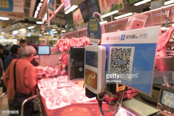 A merchant quick response code for Ant Financial Services Group's Alipay an affiliate of Alibaba Group Holding Ltd is displayed next to an Octopus...