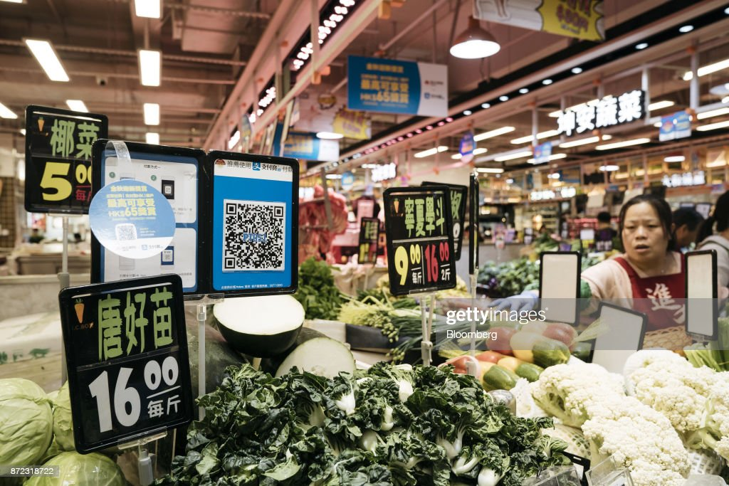 A merchant quick response (QR) code for Ant Financial Services Group's Alipay, an affiliate of Alibaba Group Holding Ltd., is displayed next to price signs at a vegetable stall inside MC Box Po Tat Market in Hong Kong, China, on Tuesday, Nov. 7, 2017. Ant Financial, which has been valued as high as $75 billion, is the world's most valuable closely held fintech company. Photographer: Anthony Kwan/Bloomberg via Getty Images
