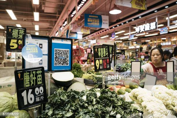 A merchant quick response code for Ant Financial Services Group's Alipay an affiliate of Alibaba Group Holding Ltd is displayed next to price signs...