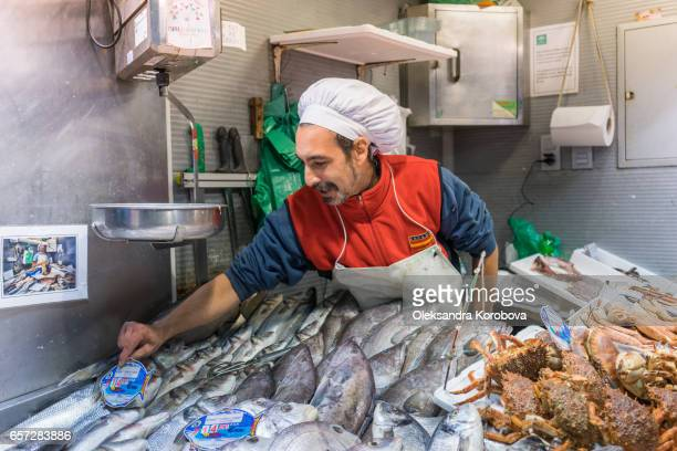 malaga, spain - december 17, 2016. merchant selling freshly caught fish, squid, crab, srimp and other seafood at a counter. vintage european fish market. - istock photos et images de collection