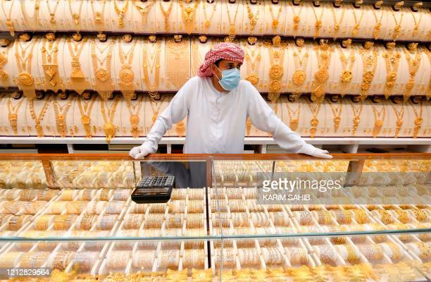 A merchant stands wearing a face mask and latex gloves due to the COVID19 coronavirus pandemic at a jeweller's shop at the Dubai Gold Souk in the...