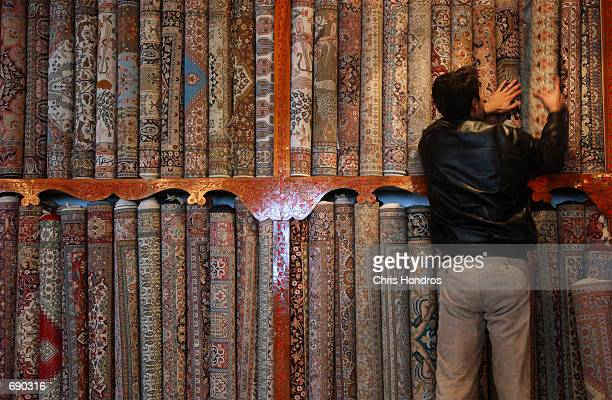 A merchant stocks up his rugs January 14 2002 in the rug district of Srinagar in the state of Kashmir which is held by India The rug industry in...