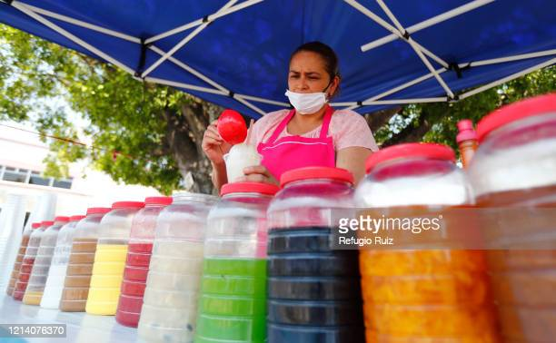 Merchant wearing a face mask prepares food as stores and markets reopen under health protocols on May 17, 2020 in Cocula, Mexico. Despite the growing...