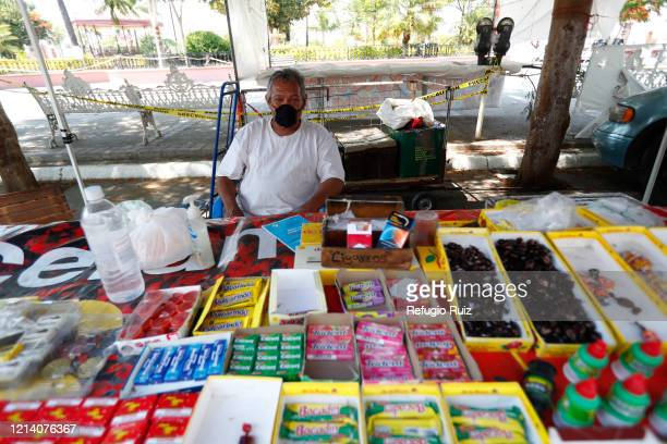 Merchant wearing a face mask sells sweets as stores and markets reopen under health protocols on May 19, 2020 in Cocula, Mexico. Despite the growing...