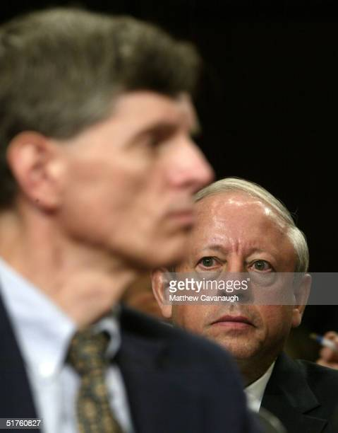 Merck Chief Executive Raymond Gilmartin sits behind the Food and Drug Administration's Dr David Graham during Graham's testimony before the Senate...
