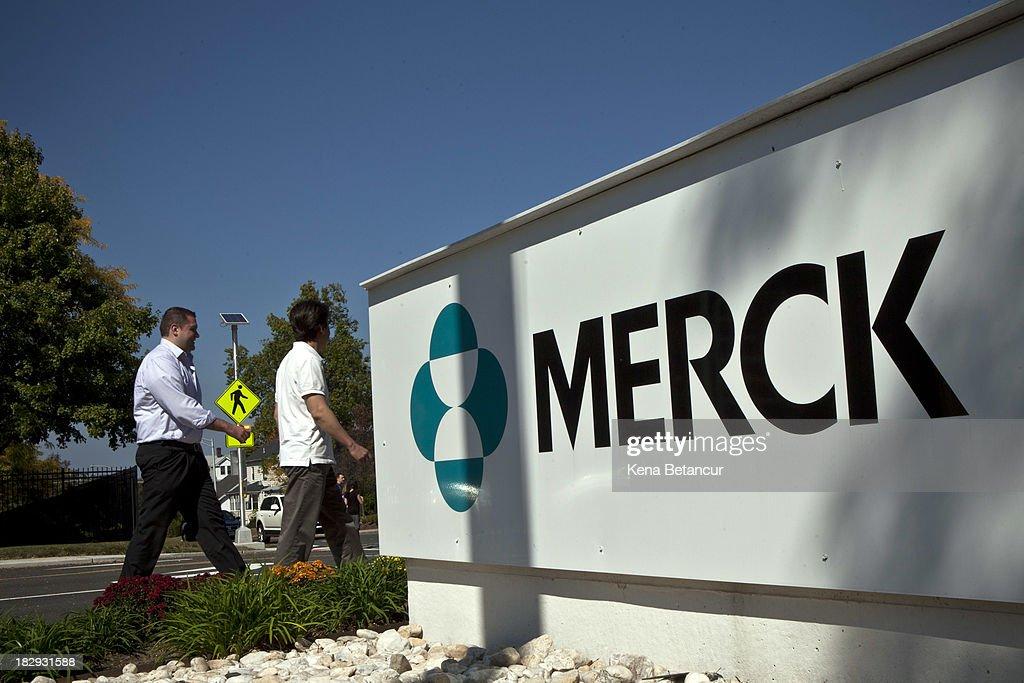 Merck employees walk past a Merck sign in front of the company's building on October 2, 2013 in Summit, New Jersey. The pharmaceutical company Merck & Co. announced today that it would cut 8,500 jobs and consolidate its real estate in Kenilworth, New Jersey instead of moving its headquarters to Summit as previously planned.