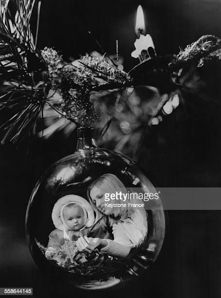 Mere et enfant se refletant dans une boule du sapin de Noel en Republique Tcheque