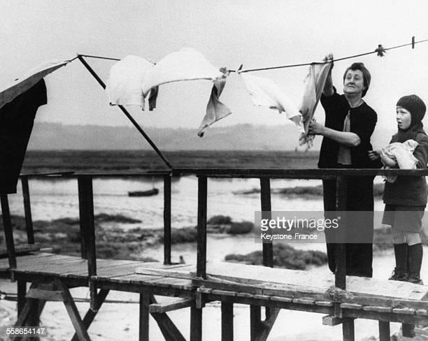 Mere et son fils essayant de faire secher leur linge sur un pont apres des inondations qui ont toute la region de l'Essex a Canvey Island RouyaumeUni...