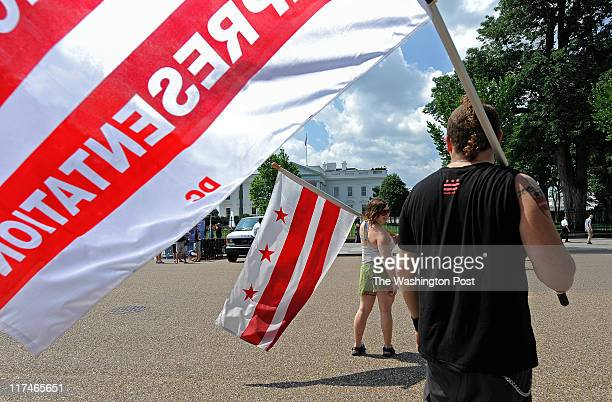WASHINGTON DC JUNE 25 Meredith Begin and Adam Eidinger hold their flags on Pennsylvania Ave in front of The White House before the rally began on...