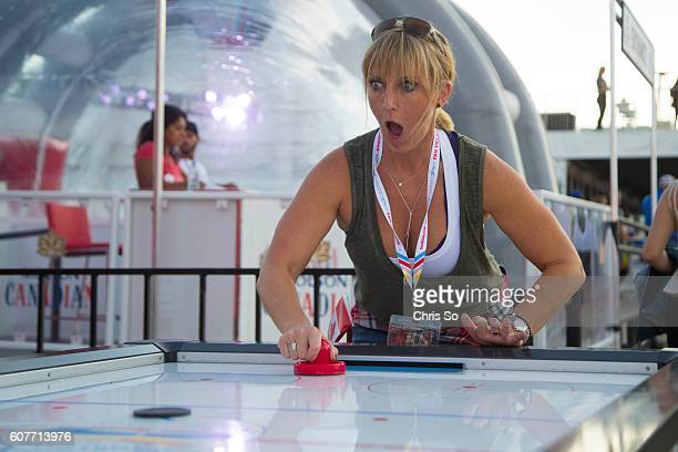 Meredith Squires reacts to a shot delivered by her son Connor on a table hockey game at World Cup of Hockey Fan Village located in the Distillery...
