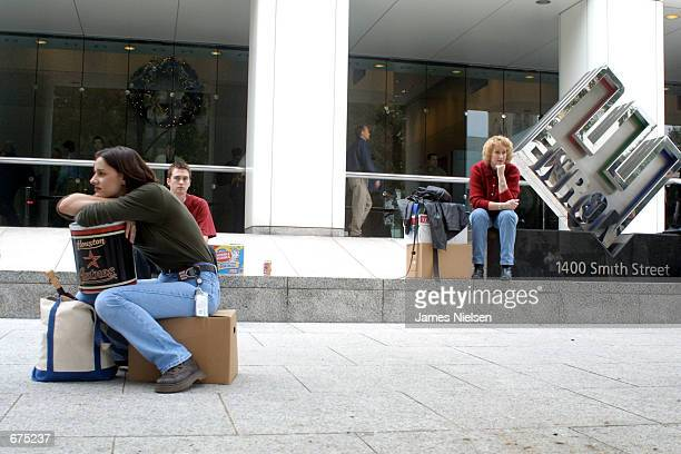 Meredith Stewart who worked in Enron's networking/data processing department sits on her personal belongings in front of the company's headquarters...
