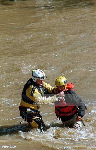 Rescue.1.0209.GF Avelino Flores is helped by Don Reyes across the L.A. RIver alongside the Golden State Freeway south of Colorado Blvd on 2/9/98....