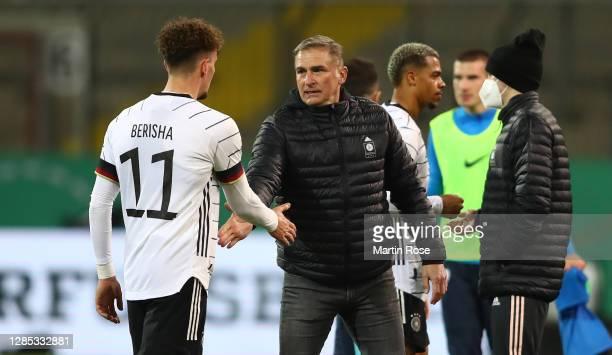 Mergim Berisha of Germany shakes hands with head coach Stefan Kuntz after the international friendly match between Germany U21 and Slovenia U21 at...