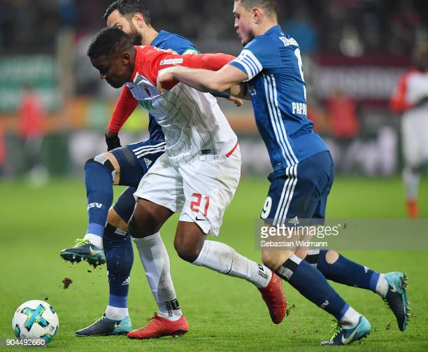 Mergim Mavraj of Hamburg Sergio Cordova of Augsburg and Kyriakos Papadopoulos of Hamburg fight for the ball during the Bundesliga match between FC...