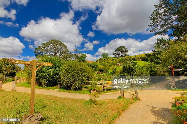 Merging dirt footpaths and signposts at entrance to rebuilt Hobbiton film set in Matamata, New Zealand, on partly cloudy summer afternoon.