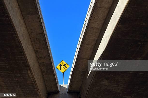 Merging sign between freeway overpass