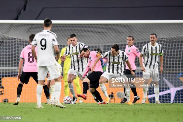 Merih Demiral and Federico Chiesa of Juventus fight for the ball with Lionel Messi of FC Barcelona during the UEFA Champions League Group G stage...