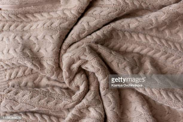 merino wool handmade knitted large blanket, super chunky yarn, trendy concept. close-up of knitted blanket, merino wool background. designer blanket made of beige smoky wool. - blanket stock pictures, royalty-free photos & images