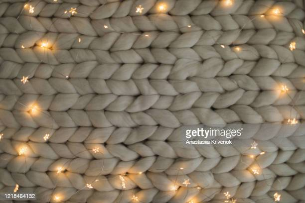 merino wool handmade knitted large blanket, super chunky yarn with led warm garland, trendy concept. close-up of knitted blanket, merino wool background. - hygge stock-fotos und bilder