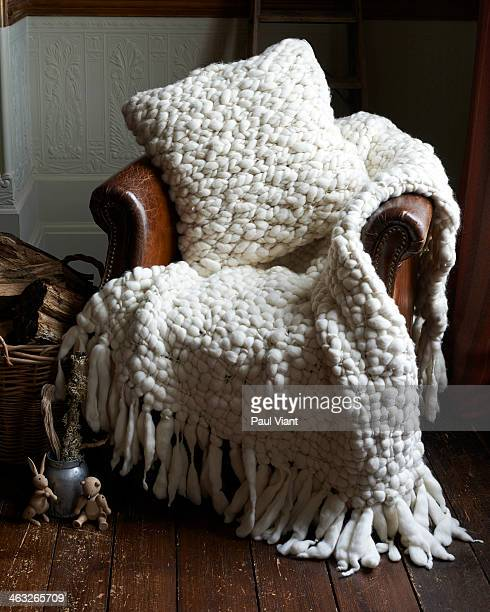 Merino wool throw and cushion on leather chair