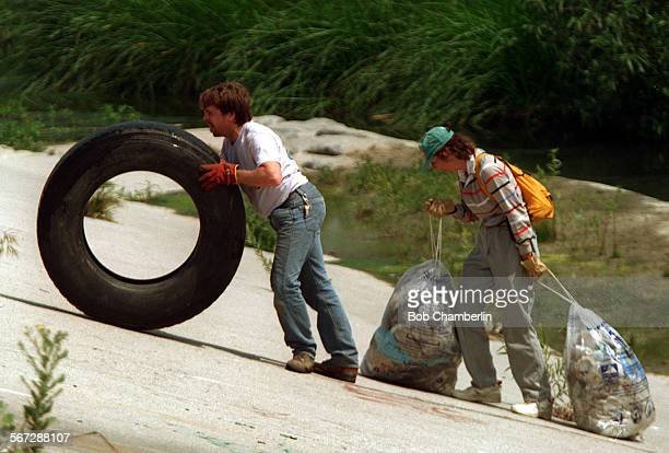 River.1.04–18.BC.c.Brian McRae of Glendale rolls giant truck tire up the steep slope of the Los Angeles River as Sallie Neubauer of Elysian Park...