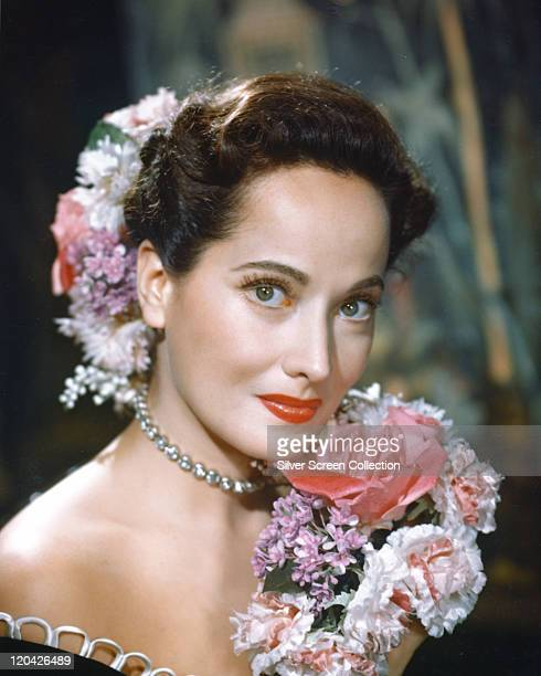 Merle Oberon British actress poses with a bouquet of flowers with flowers in her hair in a studio portrait circa 1940