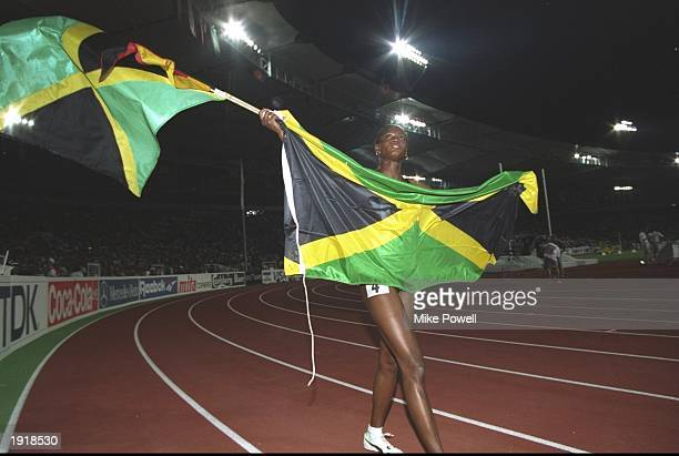 Merlene Ottey of Jamaica doing a lap of honour with her country's national flag after winning the 200 Metres event during the 1993 World...