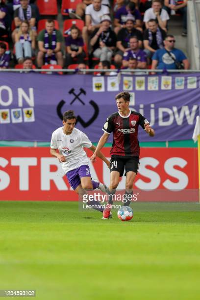 Merlin Röhl of FC Ingolstadt 04 and Dirk Carlson of Erzgebirge Aue in action during the DFB Cup first round match between FC Ingolstadt 04 and...