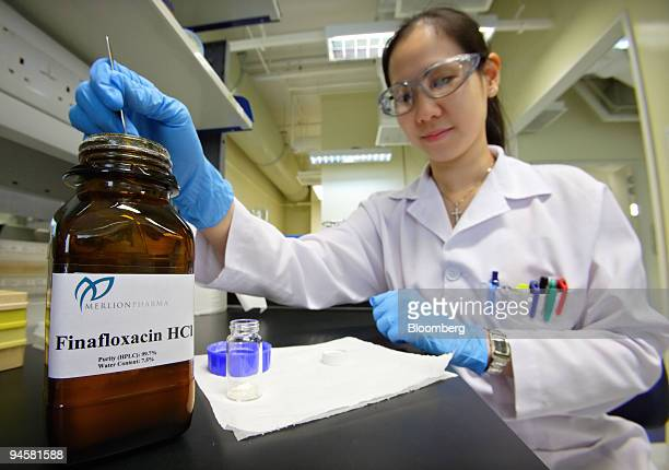 Merlion Pharmaceuticals Pte scientist measures some of the company's Finafloxacin drug developed to fight Helicobacter pylori infections which cause...