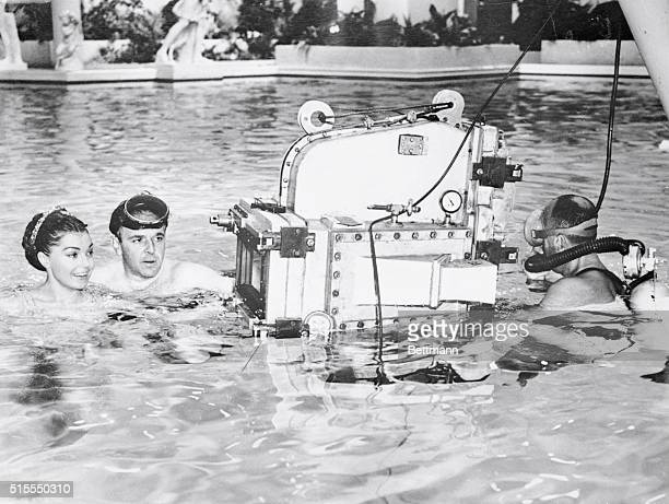 Mermaid movie star Esther Williams listens to explanations from director George Sidney about the underwater camera that will photograph the actress...