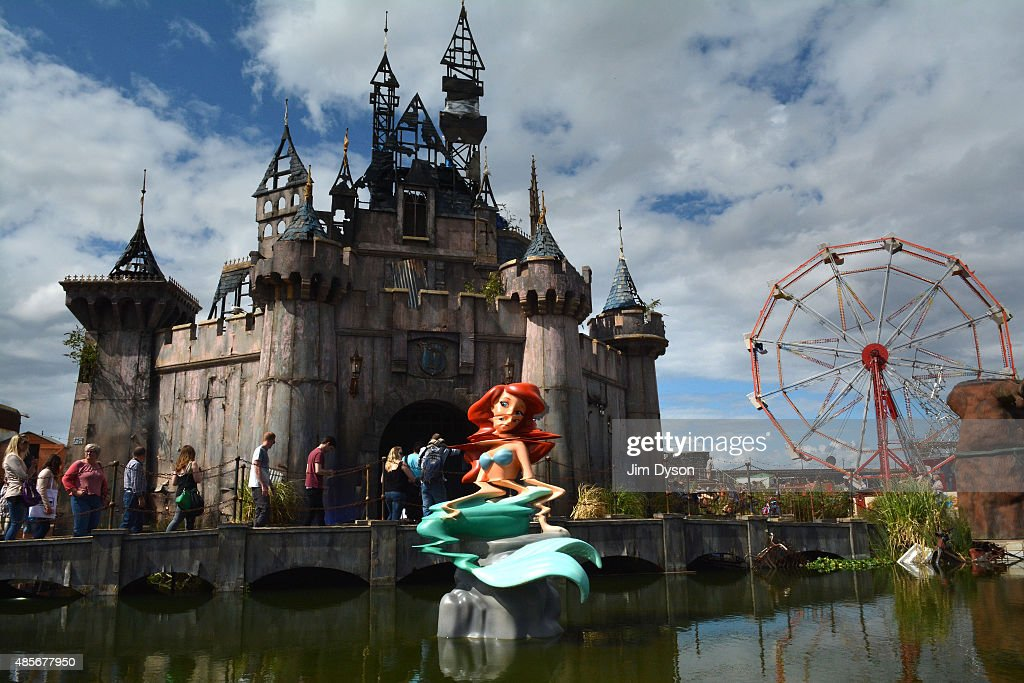A mermaid sculpture in front of the fairy castle as Banksy's Dismaland Bemusement Park opens to the public, on August 28, 2015 in Weston-Super-Mare, England. Graffiti artist Banksy has opened the subversive, pop-up theme park styled exhibition at the derelict seafront Tropicana lido, featuring the work of 50 artists. The 'Bemusement Park' combines dark humour and 'entry-level anarchism' and will open for just five weeks.