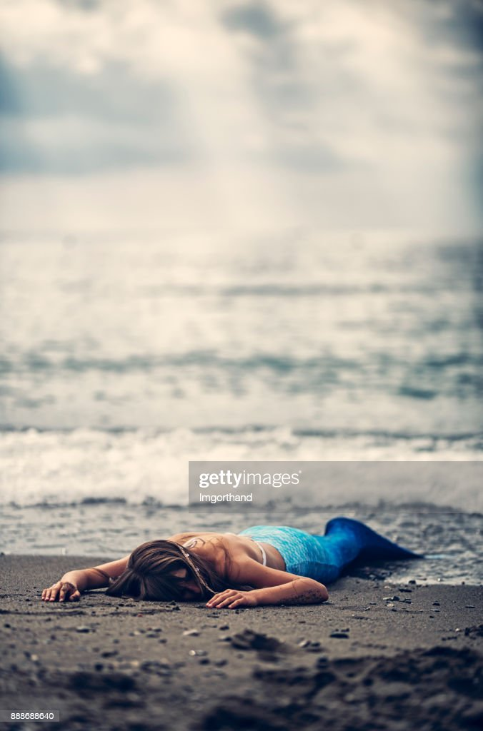 Mermaid washed up on beach : Stock Photo