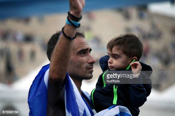 Merousis Hristoforos covered with the greek flag holds his son at the 35th Athens Classic Marathon in Athens Greece November 12 2017
