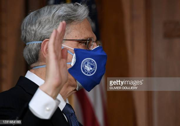 Merrick Garland raises his hand as he is ceremonially sworn in as US attorney general at the US Department of Justice on March 11, 2021 in...