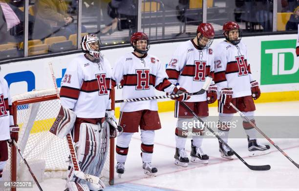 Merrick Madsen of the Harvard Crimson and his teammates Alexander Kerfoot, Devin Tringale and Phil Zielonka stand for player introductions before...