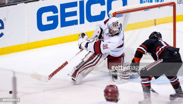 Merrick Madsen of the Harvard Crimson clears the puck during NCAA hockey in the semifinals of the annual Beanpot Hockey Tournament against the...