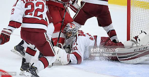 Merrick Madsen of the Harvard Crimson dives for a loose puck at the bottom of the pile during NCAA hockey against the Boston University Terriers at...