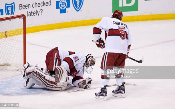Merrick Madsen of the Harvard Crimson drops to his knees in pain as the final buzzer sounds as teammate Clay Anderson checks on him against the...