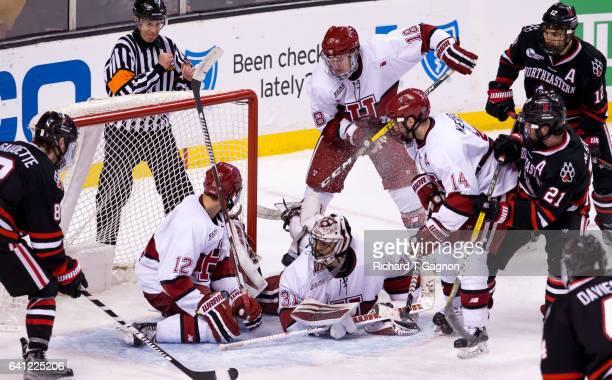 Merrick Madsen of the Harvard Crimson makes a save against the Northeastern Huskies as teammates John Marino, Adam Fox and Alexander Kerfoot fight...
