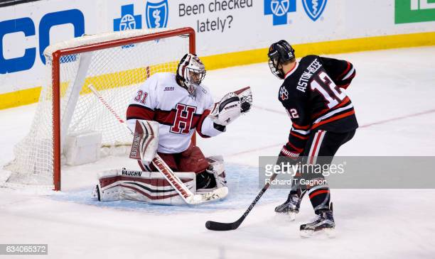 Merrick Madsen of the Harvard Crimson makes a save against Zach Aston-Reese of the Northeastern Huskies during NCAA hockey in the semifinals of the...