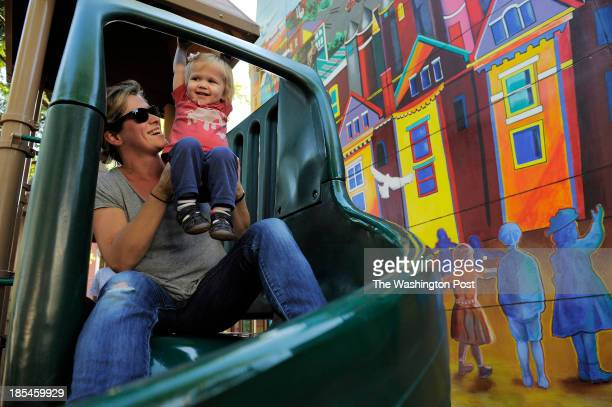 Merry Aldeman and her daughter Ginny Ritsch prepare to go down a slide in a neighborhood playground area along Westminster St NW on Monday October 14...