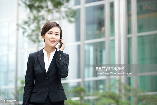Merry businesswoman on the phone outside a building, Hong Kong