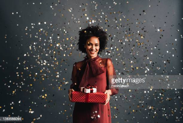merry christmas: a happy african american woman in a red festive dress holding christmas presents with confetti flying all around, a portrait - metallic dress stock pictures, royalty-free photos & images