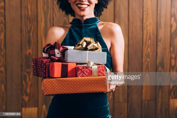 merry christmas: a n anonymous smiling elegant african american woman holding a pile of presents in her hands, a close up - stack stock pictures, royalty-free photos & images