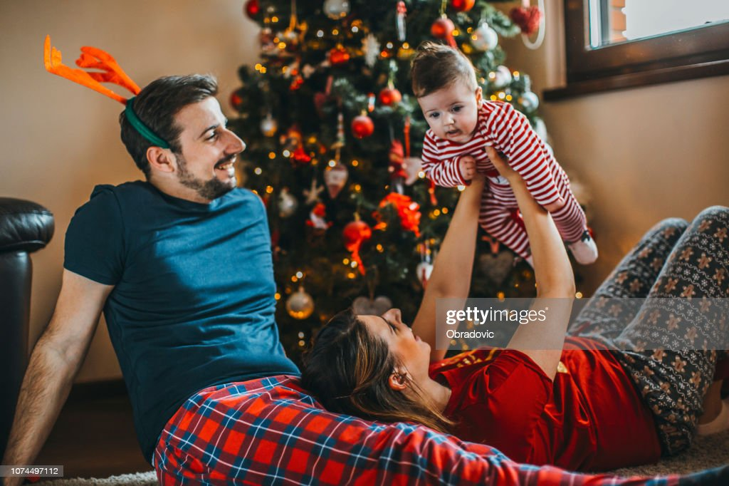 Merry Christmas! happy family mother father and child with gifts near tree : Stock Photo
