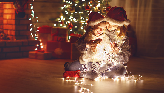 Merry Christmas! mother and child daughter with glowing garland near tree 876828410