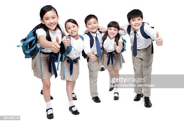Merry schoolchildren showing thumbs up with school bag on the back