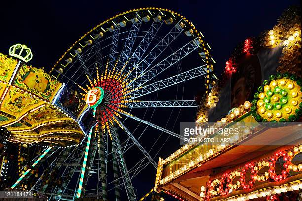 A merrygoround and fairground booths of the annual funfair 'Cranger Kirmes' are illuminated along the RhineHerne Canal in Herne western Germany on...