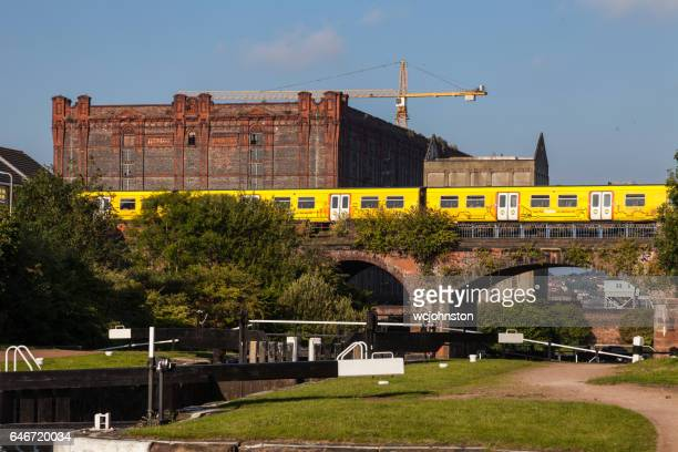 merseyrail electric train passing leeds liverpool canal at stanley dock - merseyside stock pictures, royalty-free photos & images