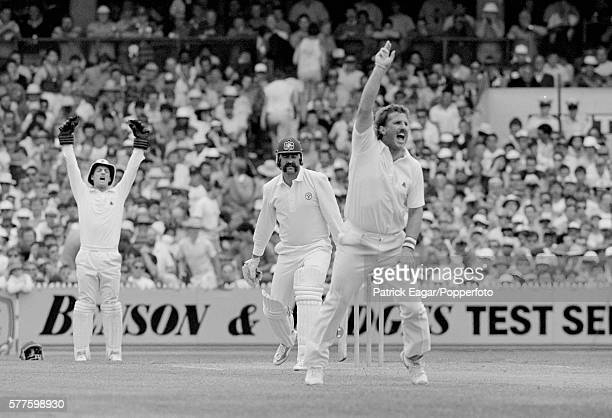 Merv Hughes of Australia is caught by England wicketkeeper Jack Richards to give Ian Botham of England his fifth wicket on the first day of the 4th...